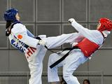 Li Zhaoyi(L) of China kicks Sharifova Shukrona of Tajikstan during Women's -44kg Taekwondo preliminary match. Sharifova won the match.
