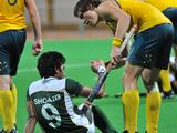 Jeremy Hayward of Australia (right) consoles Muhammad Sohaib of Pakistan after Australia beat Pakistan in the boys hockey gold medal match