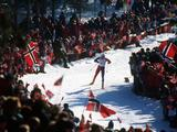 Norwegian Bjorn Daehlie passes the crowd of his national flag waving fans on his way to a gold medal in the men's 15km cross country event.