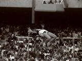 Mexico 1968:  Dick Fosbury of the USA clears the bar in the high jump competiton with his dramatic new jumping style. Under his influence the style changed from the action of a run in, with a spring off the left foot to straddle the right leg and body over the bar to the action of a run in, a take off from the left foot to pivot on the right so that his back is to the bar as the athlete rises, flicks his legs to clear the bar and fall on their back. He won with a leap of 2.24 metres and within ten years the majority of the world's jumpers had adopted the Fosbury Flop, as it became known.