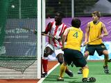 Ryan Edge (center) scored Australia's seventh goal in a Boys Preliminary Hockey match. Australia beat Ghana 8-0.