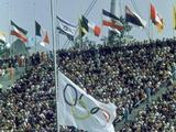 Munich 1972: A filled stadium at a memorial service for the slain Israeli athletes at the Olympic Games, with national and Olympic flags at half-mast.
