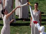 Maria Nafplotou (L), who plays the role of high priestess, passes the olympic flame to first torchbearer olympic skier Vassilis Dimitriadis (R) during the Lighting Ceremony of the Olympic Flame for the Vancouver 2010 Winter Olympic Games.(Photo by Milos Bicanski/Getty Images)