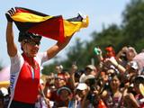 Sabine Spitz of Germany celebrates her victory in the Women's Cross Country mountain bike cycling event held at the Laoshan Mountain Bike Course.