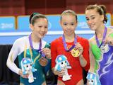 Gold medalist Tan Sixin of China (C), silver medalist Carlotta Ferlito of Italy (R) and bronze medalist Angela Donald of Australia present their medals during the awarding ceremony of women's beam final match of artistic gymnastics