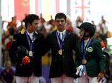 Gold medalist Marcelo Chirico of Urugary (C), silver medalist Mario Gamboa of Colombia (L) and bronze medalist Dalma Rushdi H Malhas of Saudi Arabia (R) take a group photo during the awarding ceremony of the jumping individual competition of equestrian