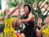 Japan's Misato Kuma (center) lays up a ball while Australia's Olivia Bontempelli (left) and Mikhaela Donnelly (far right) attempt to block in a Girls' preliminary basketball match between Japan and Australia. Japan won the match 17 - 10.