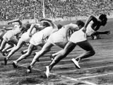 Berlin 1936: Jesse Owens (1913 - 1980) of the United States, far right, bounds off from the starting line.