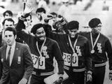 Mexico 1968:  L-R: American runners Lee Evans, Larry James and Ronnie Freeman hold their hands up in a Black Power salute while walking with an escort after the medal award ceremony The athletes competed in the final 4 x 400 meter race. Evans took the gold medal, James won the silver, and Freeman won the bronze.