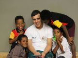 Liam Larkins watches the weightlifting competition with PNG children.