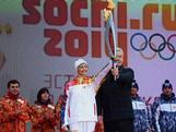 Mayor of Moscow Sergey Sobyanin and five times Olympic champion Anastasia Davidova handle a torch during of the Olympic Flame start ceremony for the XXII Winter Olympic Games Sochi 2014 along an embankment of the Kremlin on October 7, 2013 in Moscow, Russia.
