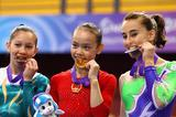 Angela Donald of Australia bronze, Sixin Tan of China gold and Carlotta Ferlito of Italy silver celebrate after the balance beam final