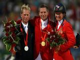 The individual jumping medal winners (L-R) Rolf-Goran Bengtsson (silver) of Sweden, Eric Lamaze (gold) of Canada and Beezie Madden (bronze) of the United States pose after the final round of the event.