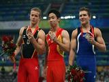 (L-R) Bronze medalist Fabian Hambuechen of Germany gold medalist Zou Kai of China and silver medalist Jonathan Horton of the United States pose with their medals after competing on high bar during the artistic gymnastics event.