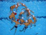 Richie Campbell #2 of Australia, center, huddles with his teammates during the men's preliminary match against Canada in the water polo event.