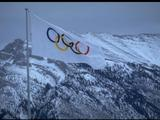 The Olympic flag blows in the strong winds of Canada in front of an impressive backdrop of snowy mountains tops.