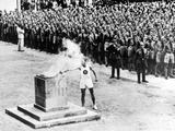 Berlin 1936: The torch, which had been lit by the sun's rays on Mount Olympus in Greece was then carried 1,800 miles by 3,000 runners through several countries, is placed by a young man in a brazier in the Lustgarten during the Opening Ceremony.