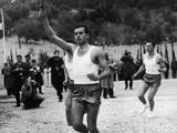 Innsbruck 1964: At Ancient Olympia, a runner carries the Olympic torch on the first leg of its journey to Athens where the flame will be flown by aircraft to Innsbruck to arrive for the 1964 Winter Olympics.
