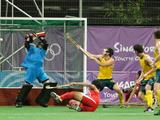 Australia's goalkeeper Daniel Beale (centre in blue) fails to stop a goal scored from a penalty corner by Singapore's Mohd Haseef Salim in the Boy's Preliminaries 3 match. Australia won the match 8-1.