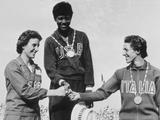 Rome 1960: The medal winners of the women's 200m sprint accept their medals. In the centre is Wilma Rudolph of the United States with her gold medal, and competitors Dorothy Hyman (left) and G Leone (right) .