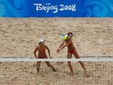 Wang Jie of China hits the ball as teammate Tian Jia looks on during the gold medal match against Kerri Walsh and Misty May-Treanor of the United States in the women's beach volleyball event held at the Chaoyang Park Beach Volleyball Ground.
