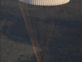 The cosmonauts parachute back to earth after taking the Torch into space.