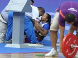 Genesis Rodriguez of Venezuela falls after she failed to lift in the women's 48kg weightlifting finals.