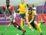 Ghana's Luke Damalie (left) vies for the ball with Australia's Dylan Wotherspoon during a preliminary boys' hockey match. Australia beat Ghana 8-0.