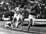 Helsinki 1952: Czechoslovakian runner Emil Zatopek (right) (1922-2000) taking the lead while competing in a track event, at the same moment, Great Britain's Chris Chataway falls as he enters the home straight. Zatopek was the first triple Olympic record holder, taking the gold medal in the 5,000m, 10,000m and marathon events.